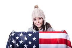 Η όμορφη πατριωτική ζωηρή νέα γυναίκα με τη αμερικανική σημαία που κρατήθηκε σε την τα χέρια που στέκονται μπροστά από Στοκ Εικόνα