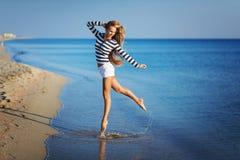 Η όμορφη προκλητική γυναίκα είναι ντυμένη σε μια γδυμένη θάλασσα φανέλλα κάθεται στα όνειρα ακτών Στοκ Φωτογραφία
