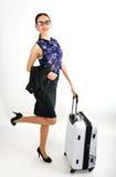 Η όμορφη προκλητική γυναίκα σε ένα επιχειρησιακό κοστούμι στέκεται δίπλα σε μια βαλίτσα και την ομιλία στο τηλέφωνο Στοκ εικόνες με δικαίωμα ελεύθερης χρήσης