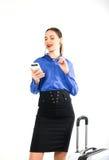 Η όμορφη προκλητική γυναίκα σε ένα επιχειρησιακό κοστούμι στέκεται δίπλα σε μια βαλίτσα και την ομιλία στο τηλέφωνο Στοκ Εικόνες