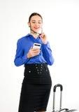 Η όμορφη προκλητική γυναίκα σε ένα επιχειρησιακό κοστούμι στέκεται δίπλα σε μια βαλίτσα και την ομιλία στο τηλέφωνο Στοκ Φωτογραφία