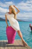 Η όμορφη προκλητική νέα γυναίκα από ξανθό σγουρό μακρυμάλλη στέκεται στο σύντομο λευκό που προκαλεί το προκλητικό ακριβό φόρεμα σ Στοκ φωτογραφία με δικαίωμα ελεύθερης χρήσης