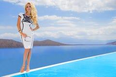 Η όμορφη προκλητική νέα γυναίκα από ξανθό σγουρό μακρυμάλλη στέκεται στο σύντομο λευκό που προκαλεί το προκλητικό ακριβό φόρεμα σ Στοκ Εικόνες