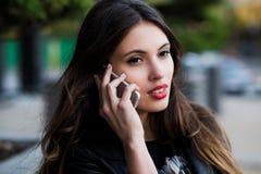 η όμορφη πόλη κυττάρων κλήσης επιχειρηματιών κάνει κινητό υπαίθριο πέρα από το τηλέφωνο Υπαίθριος, πέρα από την πόλη Στοκ Φωτογραφίες