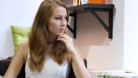 Η όμορφη σκέψη κοριτσιών στην εργασία, κάθισμα χαλαρώνει Στοκ Φωτογραφίες