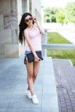 Η όμορφη στάση κοριτσιών brunette στη στάση λεωφορείου διορθώνει τα γυαλιά κρατώντας την τσάντα δέρματος, Στοκ εικόνα με δικαίωμα ελεύθερης χρήσης