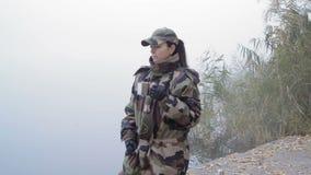 Η όμορφη στρατιωτική γυναίκα στην κάλυψη στρατού πίνει το καυτό τσάι κρατώντας μια κούπα μετάλλων στο υπόβαθρο του ποταμού στην ο φιλμ μικρού μήκους