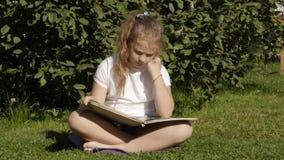 Η όμορφη συνεδρίαση έφηβη σε μια χλόη στο θερινό πάρκο και διαβάζει το βιβλίο κίνηση αργή απόθεμα βίντεο