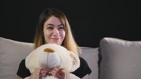 Η όμορφη συνεδρίαση γυναικών χαμόγελου στο αγκάλιασμα καναπέδων teddy αντέχει απόθεμα βίντεο
