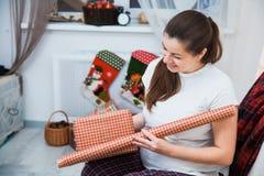 Η όμορφη συσκευασία εγκύων γυναικών παρουσιάζει για τα Χριστούγεννα, τύλιγμα δώρων Στοκ Εικόνες