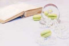 Η όμορφη σύνθεση με το γαλλικό επιδόρπιο δίπλα σε ένα μαργαριτάρι διακοσμεί με χάντρες Στοκ Εικόνες