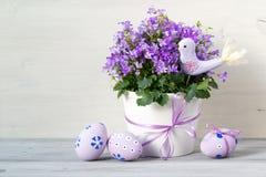 Η όμορφη σύνθεση Πάσχας στα χρώματα κρητιδογραφιών με Campanula ανθίζει, αυγά Πάσχας και κεραμικό πουλί Στοκ Εικόνες