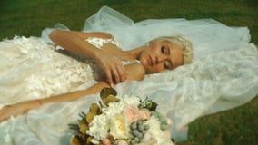 Η όμορφη τρυφερή ξανθή νύφη στο γαμήλιο φόρεμα βρίσκεται στη χλόη κοντά στη γαμήλια ανθοδέσμη απόθεμα βίντεο