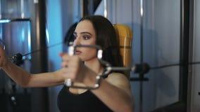 Η όμορφη φίλαθλη γυναίκα brunette είναι δεσμευμένη σε έναν προσομοιωτή για τους μυς του στήθους και των όπλων φιλμ μικρού μήκους