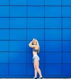 Η όμορφη φίλαθλος θέτει σε ένα μπλε υπόβαθρο Στοκ Εικόνες