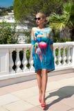 Η όμορφη φαινομενική ζαλίζοντας κομψή προκλητική ξανθή πρότυπη γυναίκα πολυτέλειας που φορά ένα φόρεμα και υψηλά τακούνια και γυα Στοκ Εικόνες
