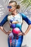 Η όμορφη φαινομενική ζαλίζοντας κομψή προκλητική ξανθή πρότυπη γυναίκα πολυτέλειας που φορά ένα φόρεμα και υψηλά τακούνια και γυα Στοκ Εικόνα