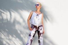 Η όμορφη φαινομενική ζαλίζοντας κομψή προκλητική ξανθή πρότυπη γυναίκα πολυτέλειας που φορά ένα κομψό κοστούμι και υψηλά τακούνια Στοκ Εικόνα