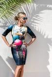 Η όμορφη φαινομενική ζαλίζοντας κομψή προκλητική ξανθή πρότυπη γυναίκα πολυτέλειας που φορά ένα φόρεμα και υψηλά τακούνια και γυα Στοκ εικόνα με δικαίωμα ελεύθερης χρήσης