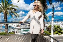 Η όμορφη φαινομενική ζαλίζοντας κομψή προκλητική ξανθή πρότυπη γυναίκα πολυτέλειας που φορά ένα παλτό και τις μπότες και τα γυαλι Στοκ Φωτογραφία