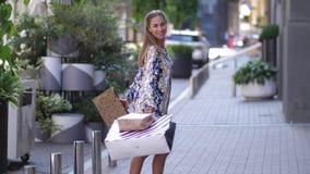 Η όμορφη χαμογελώντας γυναίκα περιστρέφει με τις τσάντες μετά από να ψωνίσει φιλμ μικρού μήκους