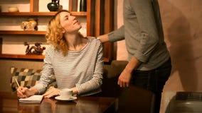 Η όμορφη χαμογελώντας γυναίκα και ο μοντέρνος άνδρας συναντιούνται στους καφέδες απόθεμα βίντεο