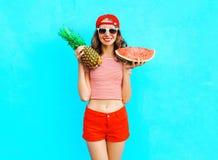 Η όμορφη χαμογελώντας γυναίκα μόδας κρατά έναν ανανά και μια φέτα του καρπουζιού Στοκ Εικόνα