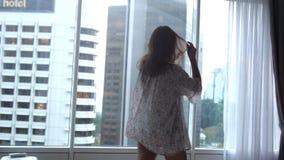 Η όμορφη χαρούμενη γυναίκα brunette χορεύει κοντά στα πανοραμικά παράθυρα απολαμβάνοντας τη μουσική στο διαμέρισμα με την άποψη π απόθεμα βίντεο
