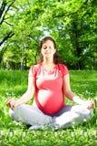 Η όμορφη χαλάρωση εγκύων γυναικών στη γιόγκα θέτει υπαίθριο Στοκ Φωτογραφία