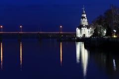 Η όμορφη χριστιανική εκκλησία στις όχθεις του ποταμού το βράδυ, με το φωτισμό, τα φω'τα απεικόνισε στο νερό ελεύθερη απεικόνιση δικαιώματος