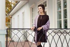 Η όμορφη όμορφη γυναίκα σε ένα καφετί φόρεμα σε ένα σάλι πέρα από τους ώμους του βγήκε στη βεράντα σε ένα κρύο πρωί φθινοπώρου στοκ φωτογραφίες