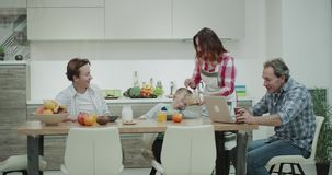 Η όμορφη ώριμη οικογένεια το πρωί έχει ένα πρόγευμα μαζί στη μεγάλη επιτραπέζια μητέρα ευτυχή να προετοιμάσει το πιάτο με φιλμ μικρού μήκους