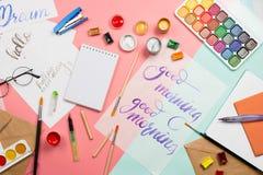 Η όμορφη flatlay ρύθμιση με τα watercolors, βούρτσες, γυαλιά, χρώματα με το handlettering καλημέρας και άλλο stati Στοκ εικόνες με δικαίωμα ελεύθερης χρήσης