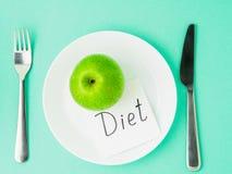Η ώριμη ακατέργαστη juicy πράσινη Apple, ολίσθηση του εγγράφου με τη διατροφή επιγραφής Στοκ Εικόνες