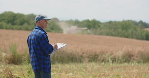 Η ώριμη αρσενική Farmer που γράφει στην περιοχή αποκομμάτων στο αγρόκτημα Σύγχρονη γεωργία απόθεμα βίντεο