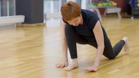 Η ώριμη γυναίκα έχει την κατάρτιση γιόγκας στη σύγχρονη γυμναστική, σε αργή κίνηση απόθεμα βίντεο
