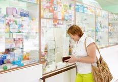 Η ώριμη γυναίκα αγοράζει τα φάρμακα Στοκ Εικόνες