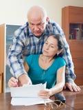 Η ώριμη γυναίκα γεμίζει τα έγγραφα, βοήθειες ανδρών αυτή στοκ φωτογραφία