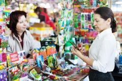 Η ώριμη γυναίκα επιλέγει τους συσκευασμένους σπόρους στοκ εικόνα