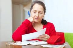 Η ώριμη γυναίκα διαβάζει τους λογαριασμούς στοκ εικόνα