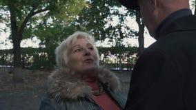 Η ώριμη γυναίκα λέει την ιστορία στον ψηλό άνδρα στο πάρκο απόθεμα βίντεο