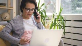 Η ώριμη επιχειρηματίας μιλά στο τηλέφωνο, χρησιμοποιώντας το lap-top στο εγχώριο εσωτερικό απόθεμα βίντεο