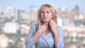 Η ώριμη επιχειρησιακή γυναίκα βήχει στο θολωμένο υπόβαθρο απόθεμα βίντεο