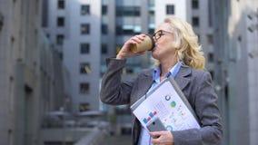 Η ώριμη επιχειρησιακή κυρία τεκμηριώνει το διαθέσιμο καφέ κατανάλωσης και χαμόγελο, έμπνευση φιλμ μικρού μήκους