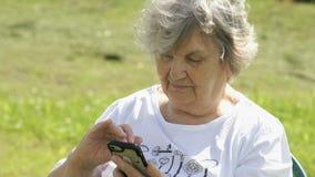 Η ώριμη ηλικιωμένη γυναίκα κρατά ένα κινητό τηλέφωνο υπαίθρια απόθεμα βίντεο
