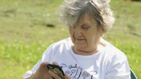 Η ώριμη ηλικιωμένη γυναίκα κρατά ένα smartphone υπαίθρια φιλμ μικρού μήκους