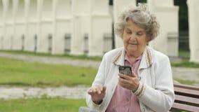 Η ώριμη ηλικιωμένη γυναίκα κρατά το ασημένιο έξυπνο τηλέφωνο υπαίθρια απόθεμα βίντεο