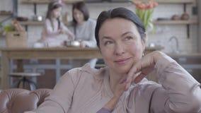 Η ώριμη συνεδρίαση γυναικών πορτρέτου στον καναπέ, θυμάται τις προηγούμενες ημέρες με το χαμόγελο και τις ευχαριστίες Στο υπόβαθρ απόθεμα βίντεο