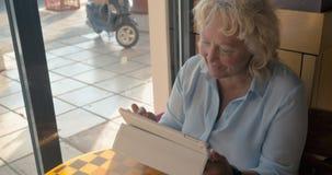 Η ώριμη συνεδρίαση γυναικών σε έναν καφέ και απολαμβάνει την ταμπλέτα της , έξω από το παράθυρο το καλοκαίρι, ηλιόλουστη ημέρα απόθεμα βίντεο