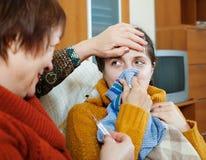 Η ώριμη φροντίδα γυναικών για την ενήλικη κόρη της έχει το κρύο στοκ φωτογραφία